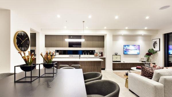 Modern living room with a television beside dinner and kitchen, the dining table has creative and fancy plants made.